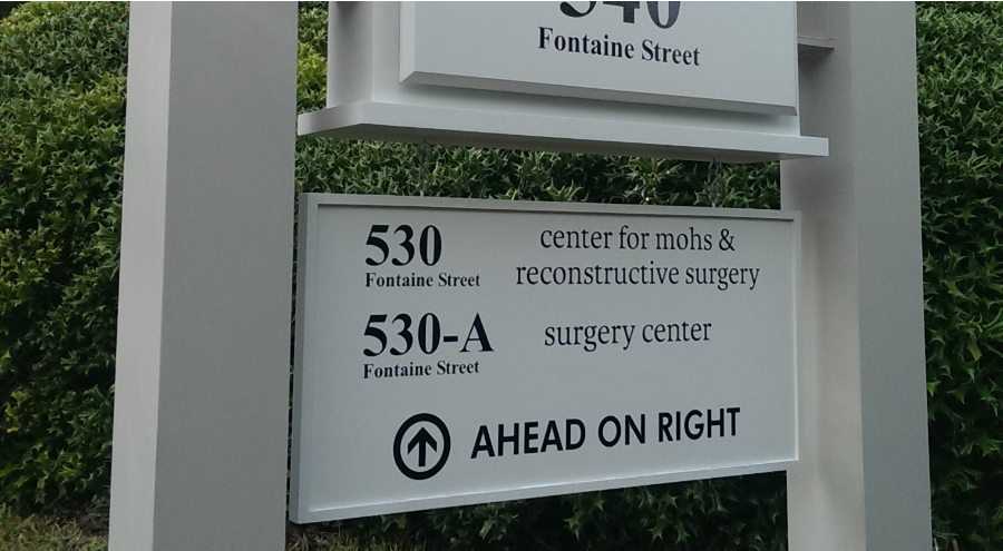Exterior wayfinding medical facility directional signage with arrow by Pensacola Sign